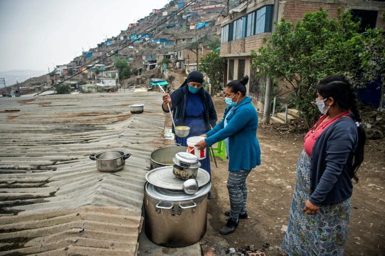 Religiosa serve sopa para moradores da comunidade Pamplona Alta, sudoeste de Lima, em maio de 2020