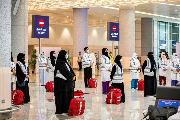 Membros da equipe médica do Ministério Saudita do Haje aguardam o primeiro grupo de peregrinos no Aeroporto Internacional de Jidá
