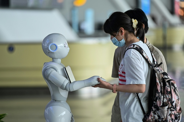 Passageiro usando máscara contra a Covid-19 utiliza os serviços de informação de um robô no Tianhe Airport em Wuhan, na China