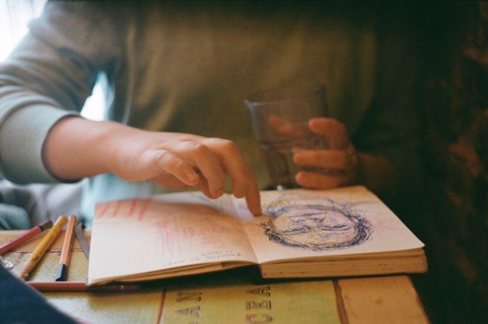 A artista Erin McAtee, de Nova York, aponta para um retrato em seu caderno de rascunhos