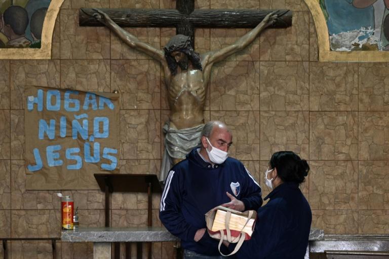O padre Lorenzo De Vedia, conhecido como 'padre Toto', entrega cinzas de vítima do coronavírus na capela Virgen de Caacupé, na villa 21 de Buenos Aires