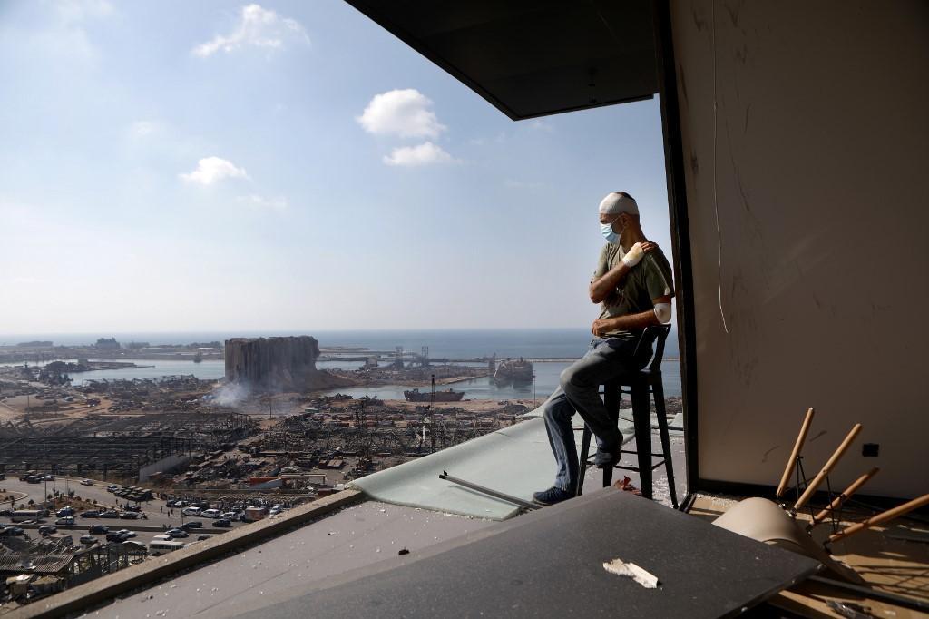 O produtor de TV libanês Tony Ahwaji, ferido, contempla na varanda de seu apartamento danificado a devastação da cidade de Beirute