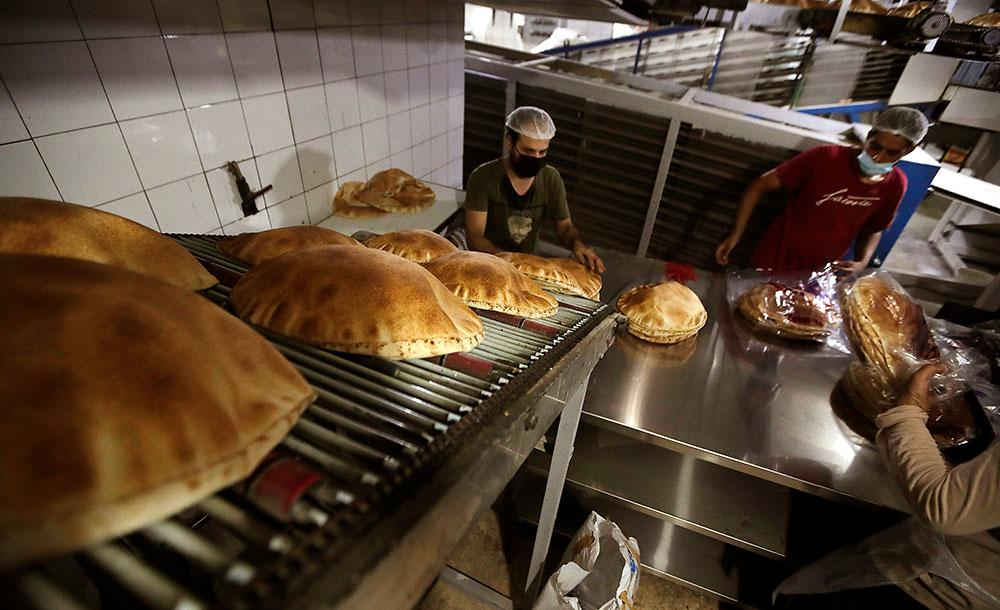 Funcionários de padaria trabalham fabricação de pão: falta de trigo pode provocar fome