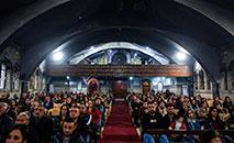 Cristãos na Igreja siríaco-carólica Mart Sarah, em Qaraqosh, seriamente danificada durante presença do autoproclamado Estado Islâmico (AFP)