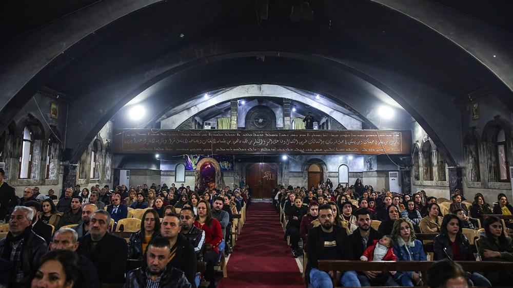 Cristãos na Igreja siríaco-carólica Mart Sarah, em Qaraqosh, seriamente danificada durante presença do autoproclamado Estado Islâmico
