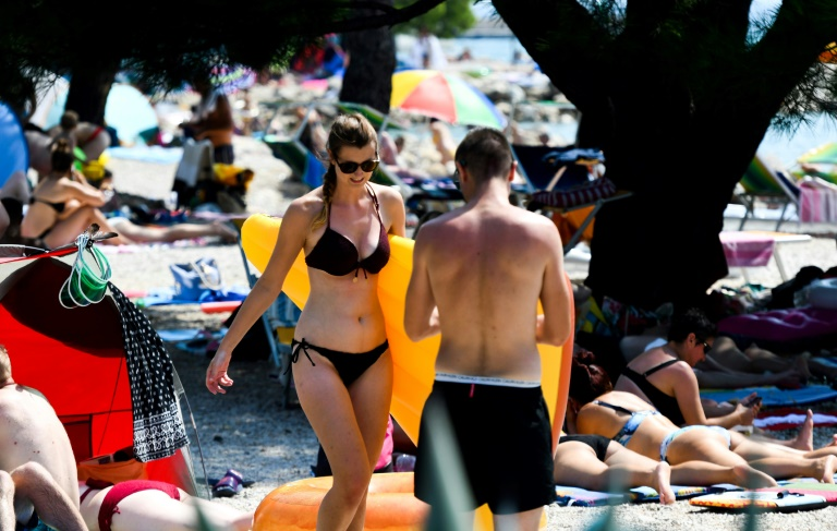 Multidões aproveitam a praia, tomam banho de sol e nadam no mar em 13 de agosto de 2020, em Crikvenica, na costa norte do Adriático, na Croácia