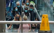 Passageiros usando máscaras protetoras em escada rolante na estação St Pancras, em Londres (Tolga Akmen/AFP)