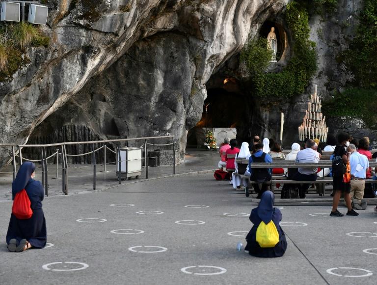 Peregrinos rezam diante da Gruta do Santuário de Lourdes, sul da França, em 14 de agosto de 2020
