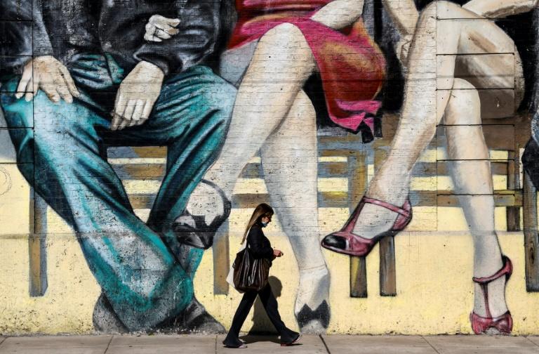 Mulher caminha por mural que alude ao tango em Buenos Aires