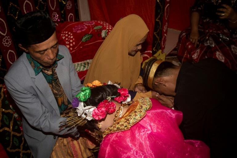 Jovem de 18 anos e seu marido de 21 após casamento no vilarejo de Tampapadang, Indonésia