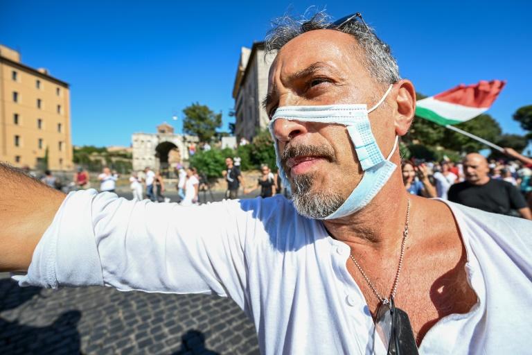Um homem usando uma máscara facial recortada participa de um protesto de movimentos contra o uso de máscaras, negacionistas da covid-19, anti-5G e antivacinação, em 5 de setembro de 2020, em Roma