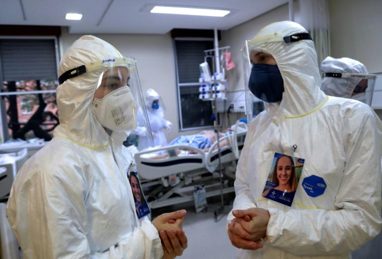 Profissionais de saúde conversam enquanto um paciente infectado com covid-19 é atendido na Unidade de Terapia Intensiva da Santa Casa de Misericórdia de Porto Alegre, Brasil, em 13 de agosto de 2020