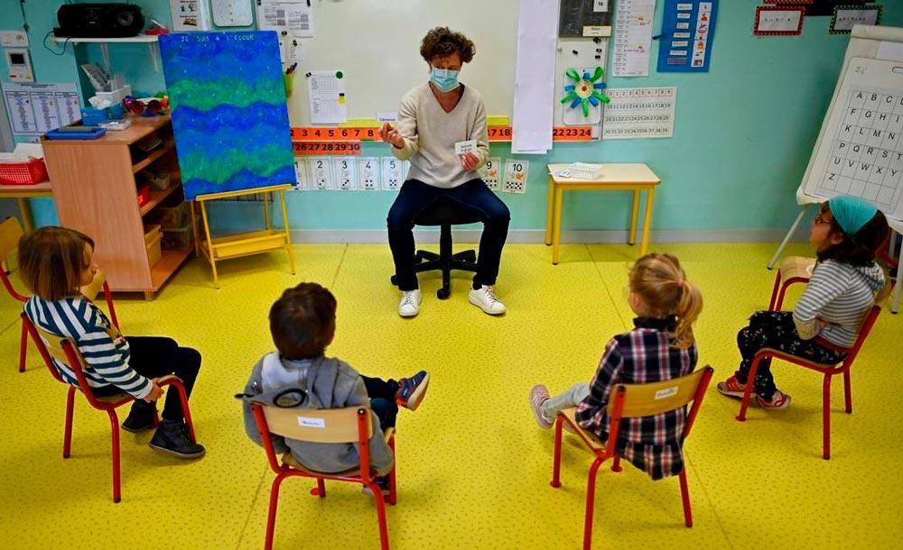 No interior da França, alunos assistem à aula de professor usando uma máscara protetora