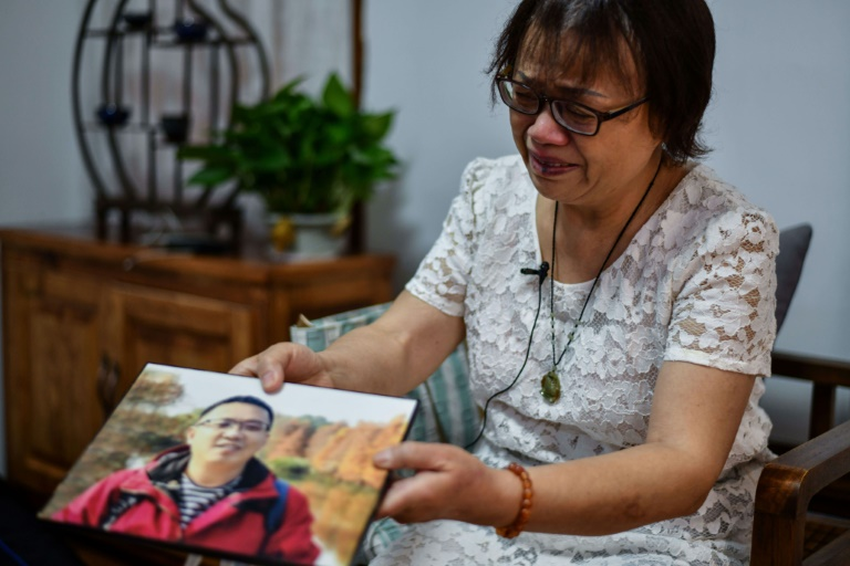 Zhong Hanneng mostra uma foto do filho, que morreu vítima de covid-19, em um encontro em Wuhan, China, em 6 de setembro de 2020