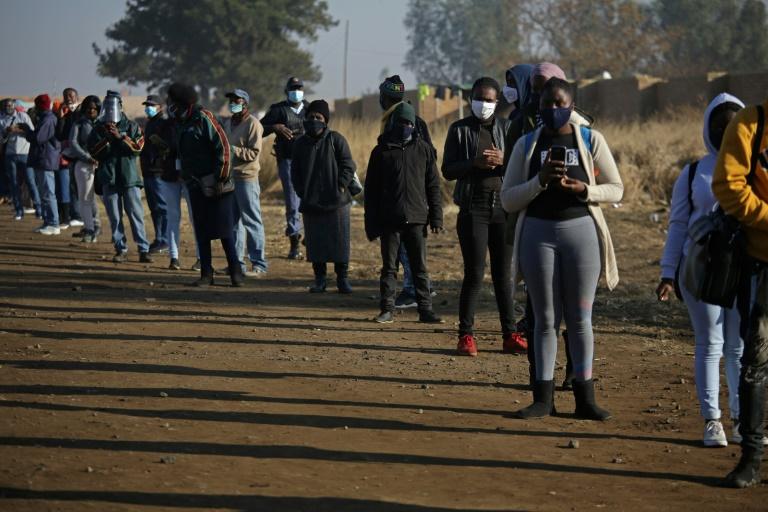 Sul-africanos fazem fila em frente à estação ferroviária Pienaaspoort, a leste de Pretória, para embarcar em trens de passageiros em 1ºde julho de 2020, na retomada das operações locais