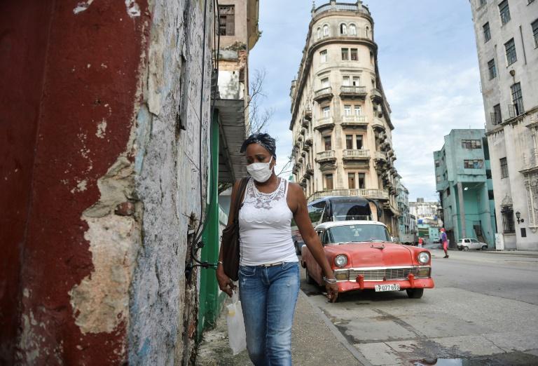 Mulher caminha de máscara pelas ruas do centro velho de Havana