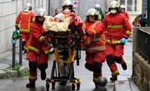 Bombeiros carregam ferido perto da antiga sede da revista satírica 'Charlie Hebdo' (Alain Jocard/AFP)