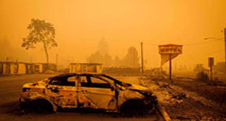 Veículo incendiado é visto no estacionamento de hotel em Gates, no Oregon (Katheryn Elsesser/AFP)