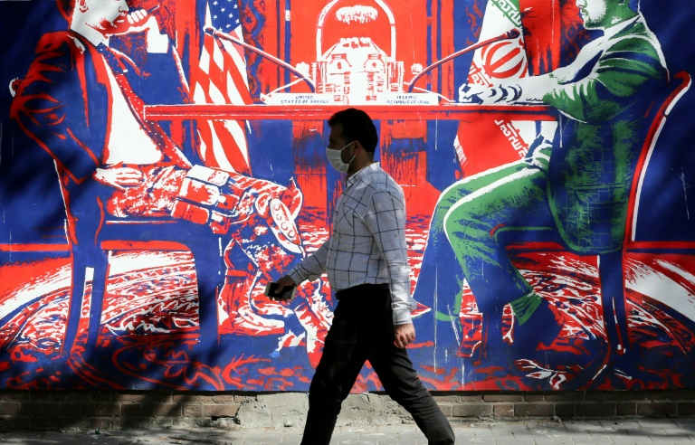 Homem passa por mural pintado nas paredes da antiga embaixada dos Estados Unidos em Teerã