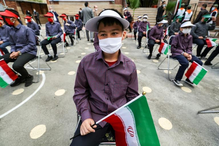 Crianças com máscara seguram bandeira iraniana na volta às aulas no Irã
