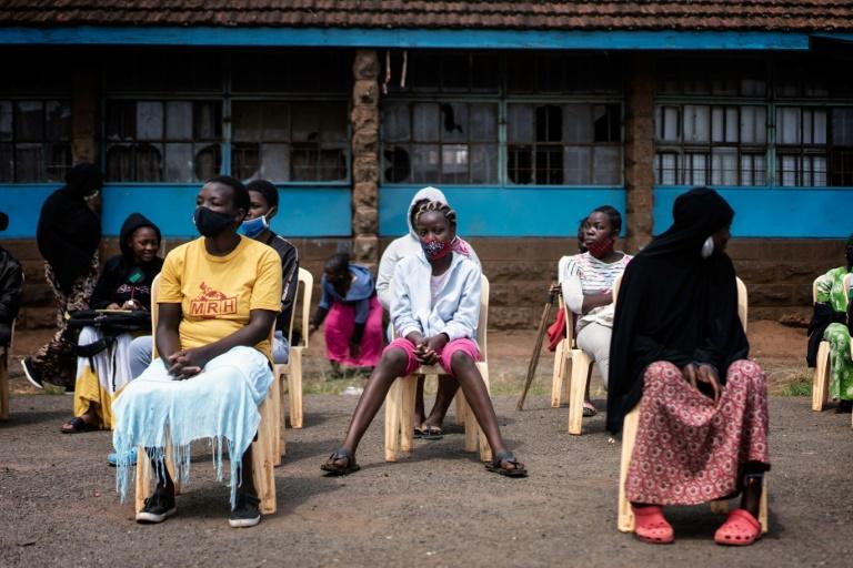 Meninas com máscara aguardam para receber absorventes em escola da Kibera, em Nairóbi