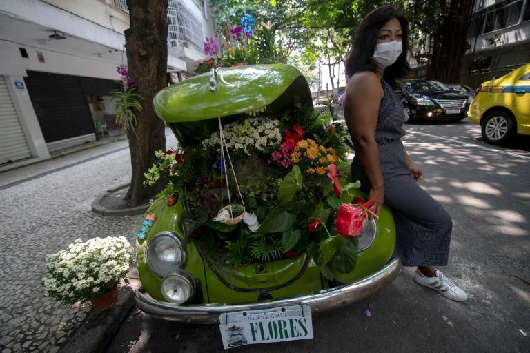 A florista Roberta Machado ao lado de seu Fusca de 1969, que transformou em uma floricultura ambulante