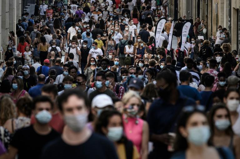 Pedestres, alguns com máscara, caminham por rua comercial em Bordeaux, na França