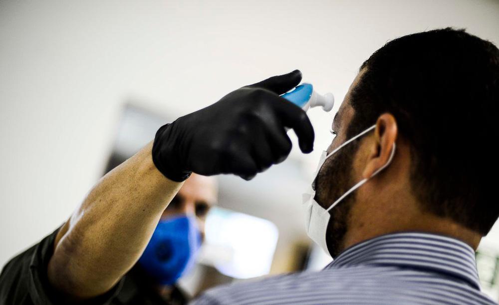 Funcionário de agência bancária mede temperatura de cliente, em São Paulo