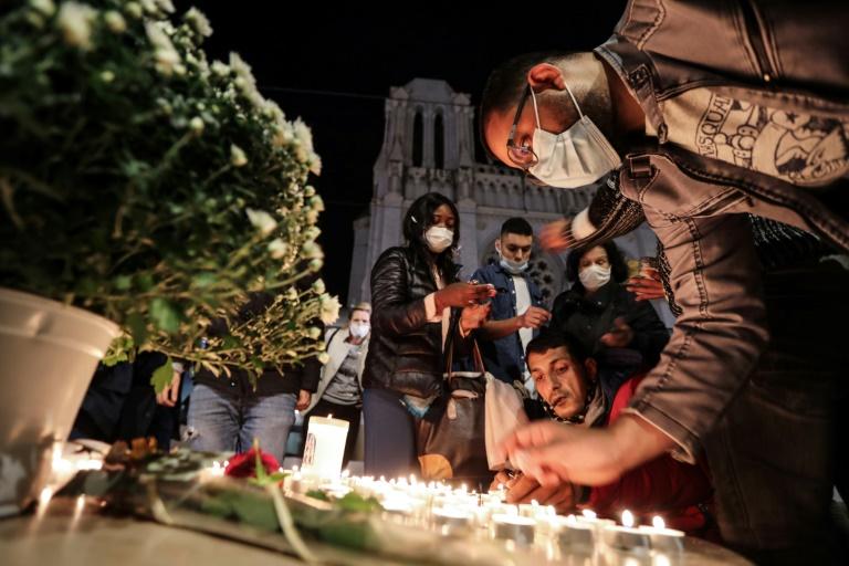 Pessoas acendem velas em homenagem aos mortos no ataque à Basílica de Notre-Dame, em Nice