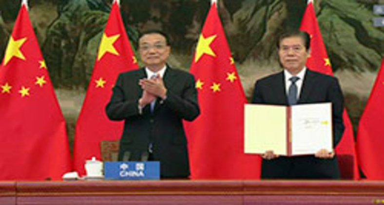 O premiê Li Keqiang (à esquerda) na cerimônia de assinatura do RCEP no Grande Salão do Povo em Pequim no domingo, 15 de novembro de 2020 (AFP/Eyepress)