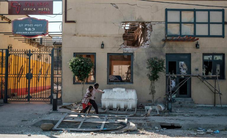 Dois garotos brincam em frente a hotel danificado por bombardeios em Humera, na Etiópia