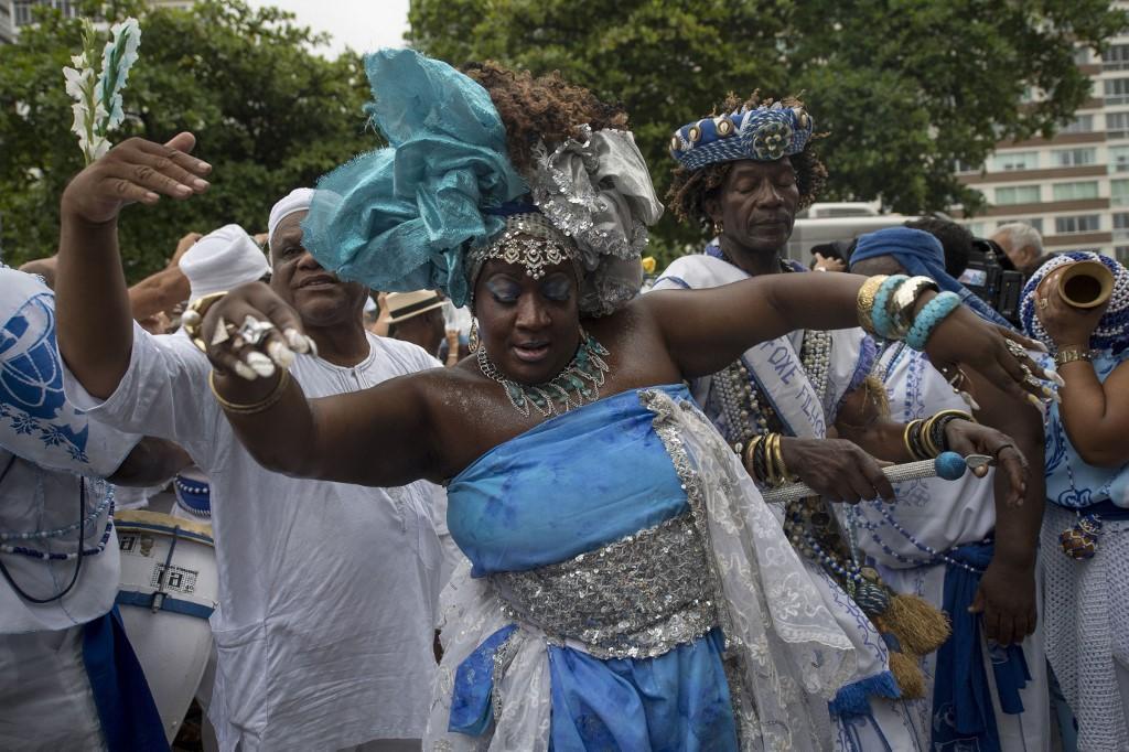 Umbandistas cantam e dançam como parte de culto religioso de fim de ano dedicado a Iemanjá na Praia de Copacabana no Rio de Janeiro