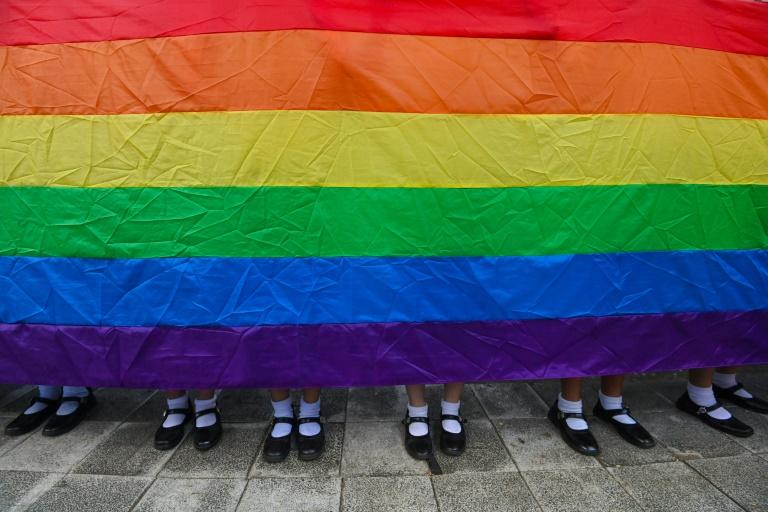 Estudantes seguram a bandeira do arco-íris em apoio ao movimento LGBT fora do Ministério da Educação em Bangcoc