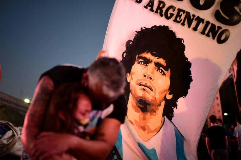 Um homem e sua filha choram a morte de Diego Maradona, reunidos com uma multidão em Buenos Aires