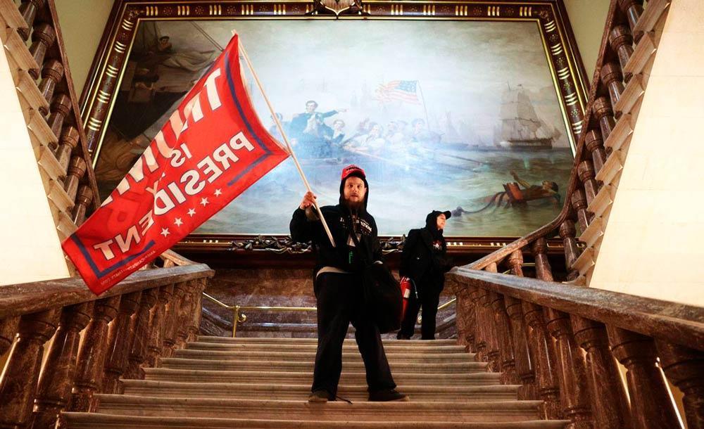 Manifestante pró-Trump acena bandeira em escadas do Capitólio, após invasão