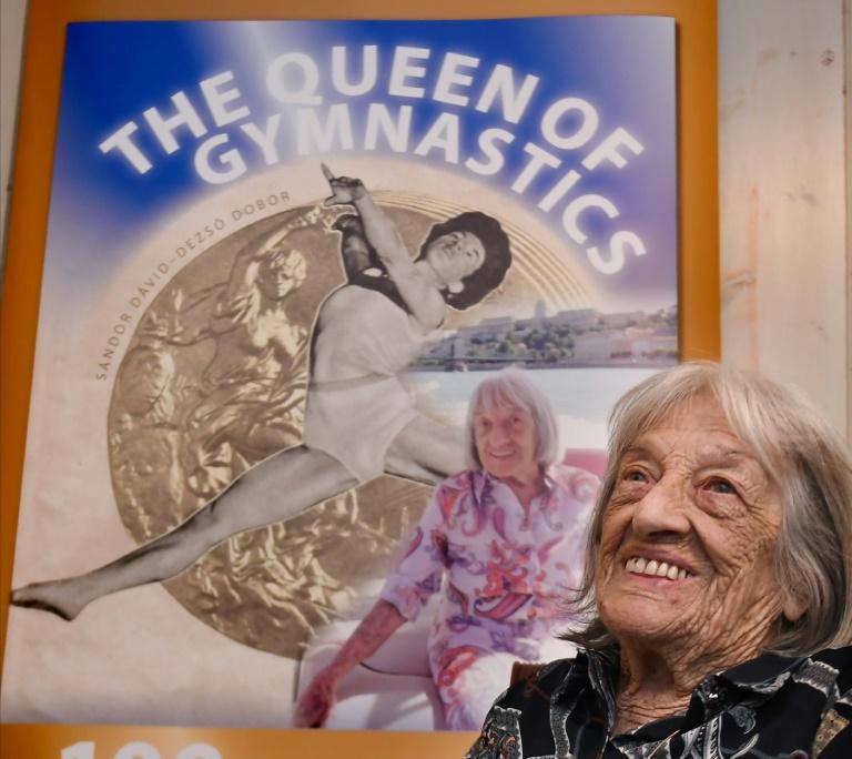 A campeã olímpica húngara Agnes Keleti em frente a um pôster com sua biografia, lançada para comemorar seu centésimo aniversário, em 6 de novembro de 2020 em Budapeste