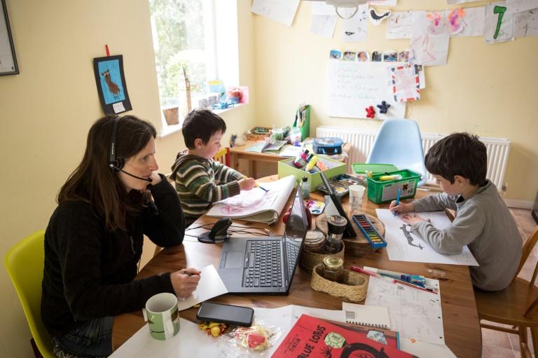 Teletrabalhadora com seus filhos fazendo cursos em casa, algo sobre o qual a ONU alerta