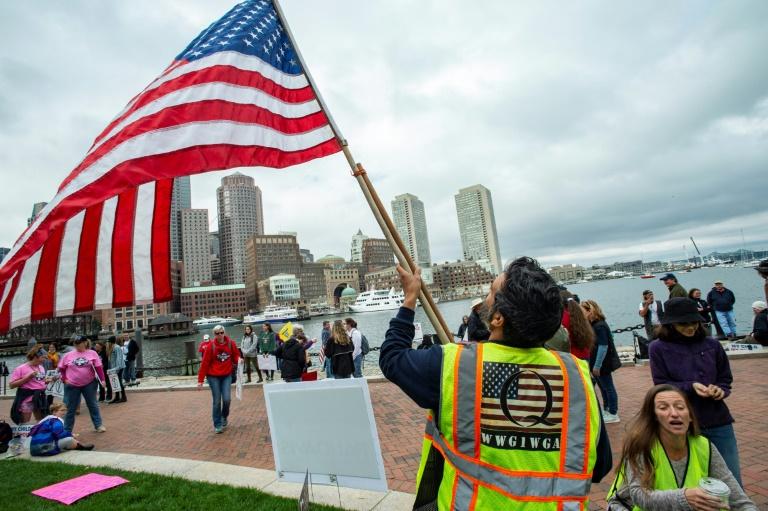 Um homem com um colete QAnon agita uma bandeira dos EUA enquanto manifestantes se reúnem em 5 de outubro de 2020 para protestar contra as vacinas obrigatórias contra gripe para crianças em Boston, Massachusetts