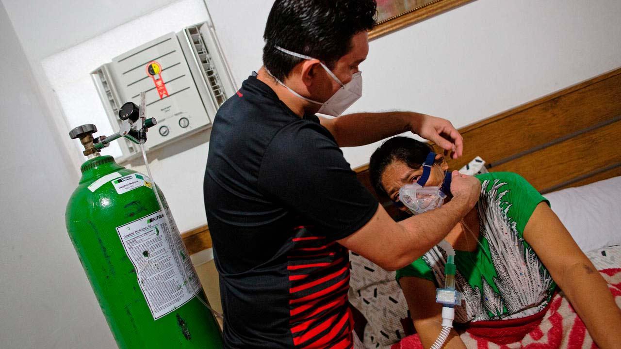 Médico Marcos Fonseca Barbosa ajuda sua mãe com oxigênio: ele teve que cuidar dela em casa por falta de vaga em hospital