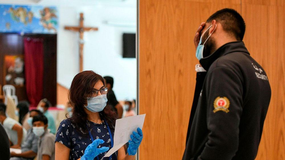 Profissional de saúde conversa com pessoa prestes a receber uma dose de uma vacina contra o coronavírus na Igreja de São Paulo em Abu Dhabi