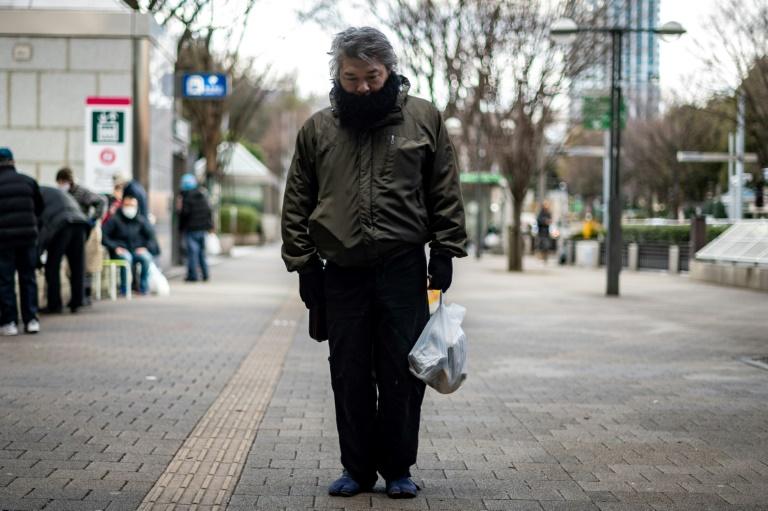 Yuichiro carrega bolsa de comida distribuída por organização em Tóquio, Japão, em 9 de janeiro