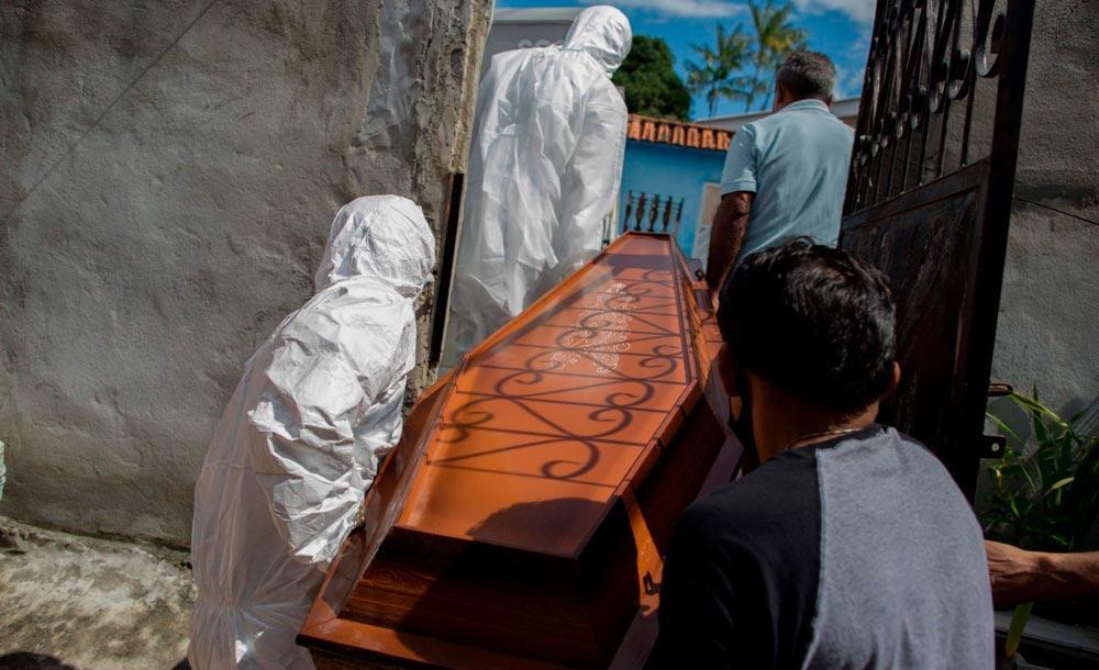 Agentes funerários municipais carregam caixão de vítima daCovid-19 em Manaus