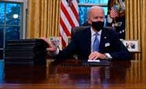 O presidente Joe Biden se prepara para assinar uma série de decretos no Salão Oval da Casa Branca (Jim Watson/AFP)