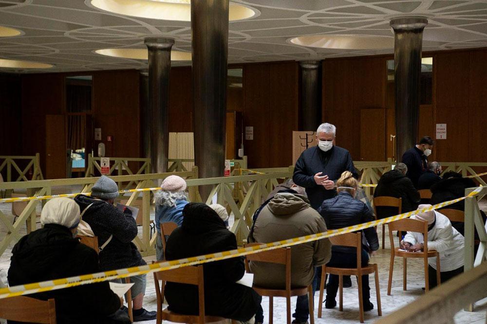O cardeal Konrad Krajewski, o esmoleiro papal, ajuda os desabrigados que recebem a primeira dose da vacina contra a Covid-19 no átrio da sala Paulo VI no Vaticano em 20 de janeiro de 2021.