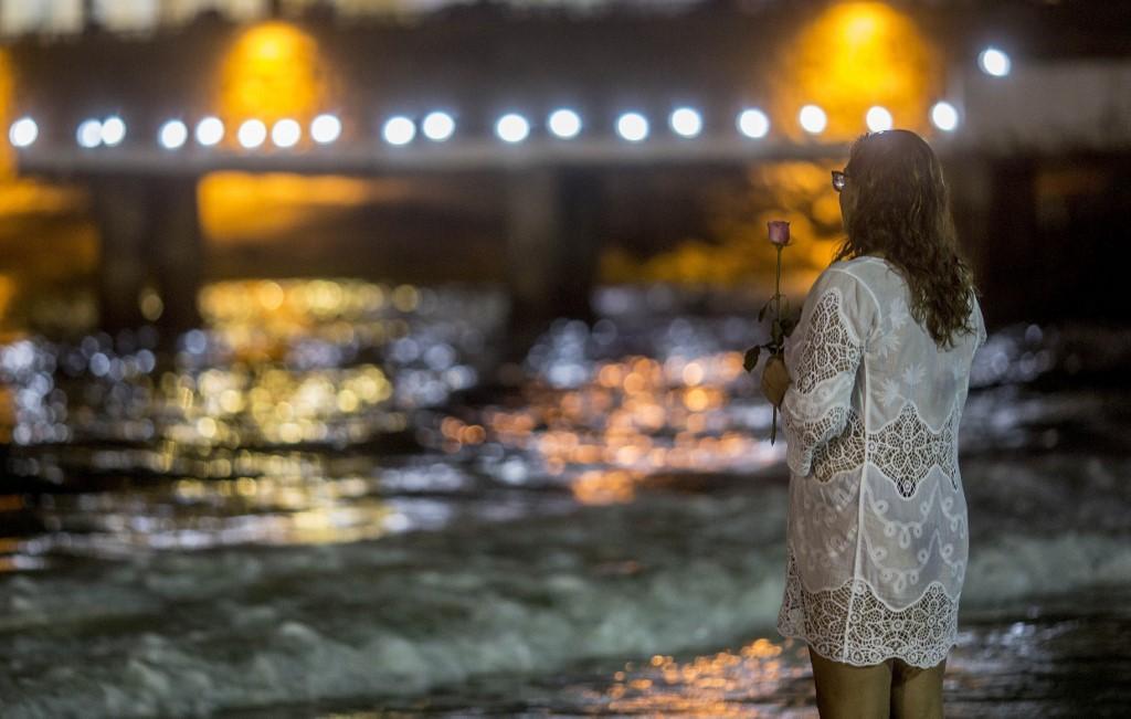 Mulher segura uma rosa antes de jogá-la na água para Iemanjá antes das comemorações de Ano Novo na Praia de Copacabana, no Rio de Janeiro, Brasil, em 31 de dezembro de 2019