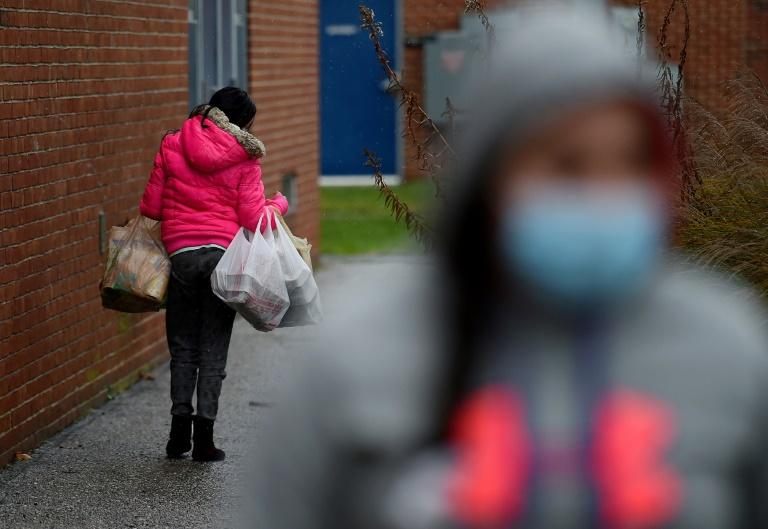 Um transeunte carrega alimentos coletados em um centro de caridade em Baltimore