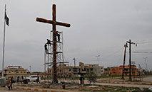 Voluntários da cidade de Qaraqosh constroem cruz gigante na estrada principal enquanto tentam retornar à vida normal após serem expulso pelo Estado Islâmico em 2016 (AFP/Ahmad Gharabli)