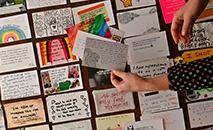 Eleanor Tattersfield mostra os cartões postais nos quais os britânicos escreveram seus segredos de confinamento, em 22 de março de 2021 em Londres (Ben STANSALL/AFP)