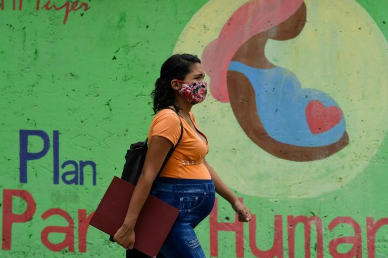 Uma mulher grávida usando uma máscara facial passa por um mural