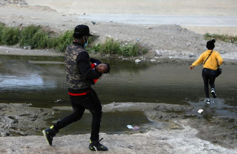 Um casal de migrantes haitianos cruza o rio Grande na tentativa de chegar aos Estados Unidos, perto de El Paso, em Ciudad Juárez, México, em 15 de abril de 2021